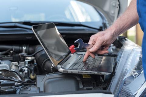 Mechanic using laptop for checking car engine