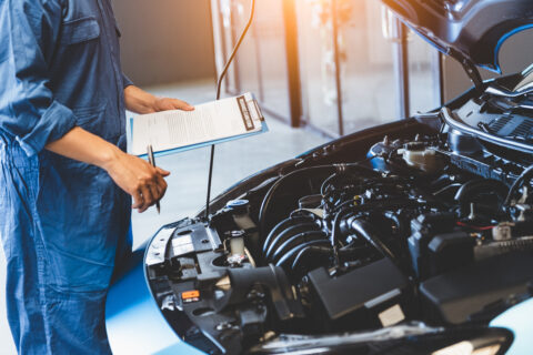 Car mechanic holding clipboard and checking to maintenance vehicle by customer claim order in auto repair shop garage.