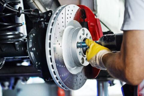 Car mechanic in a garage repairs a brake