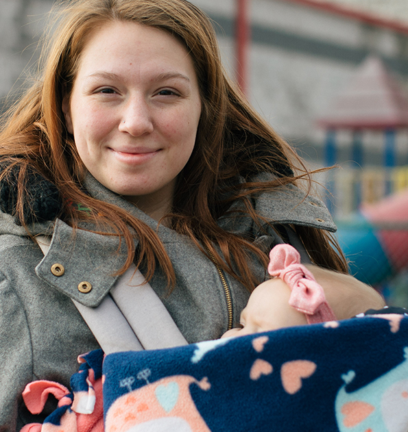 Photo of a caucasian woman with long reddish hair, smiling at the camera, with a baby in a carrier on her chest.