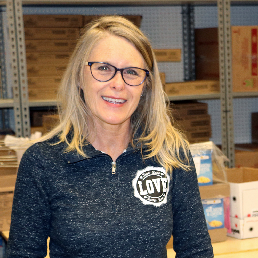 Image of smiling woman with long blonde hair and glasses, facing the camera with shelves of boxes in the background