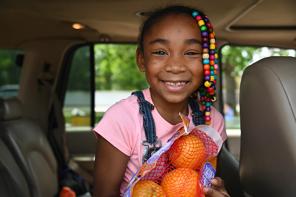 Photo of young Black girl smiling, holding a bag or oranges. She is wearing a pink shirt and has colorful beads in her hair.
