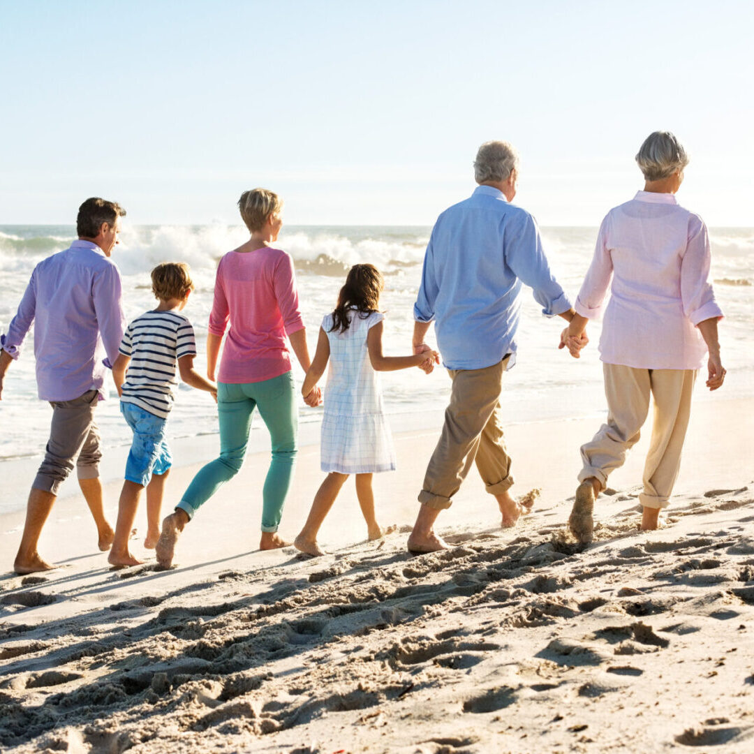 Rear view of multi-generation holding hands while walking on beach. Horizontal shot.