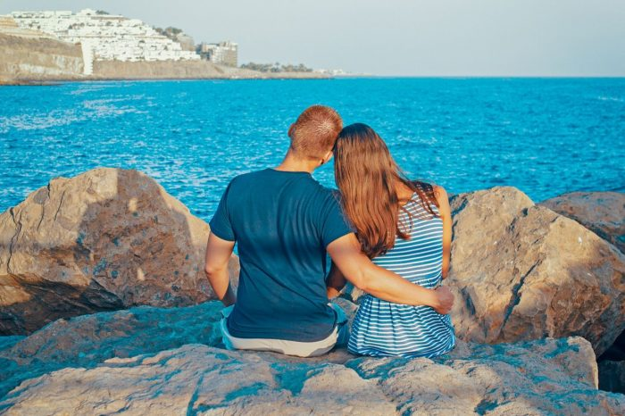 man & woman hugging by ocean