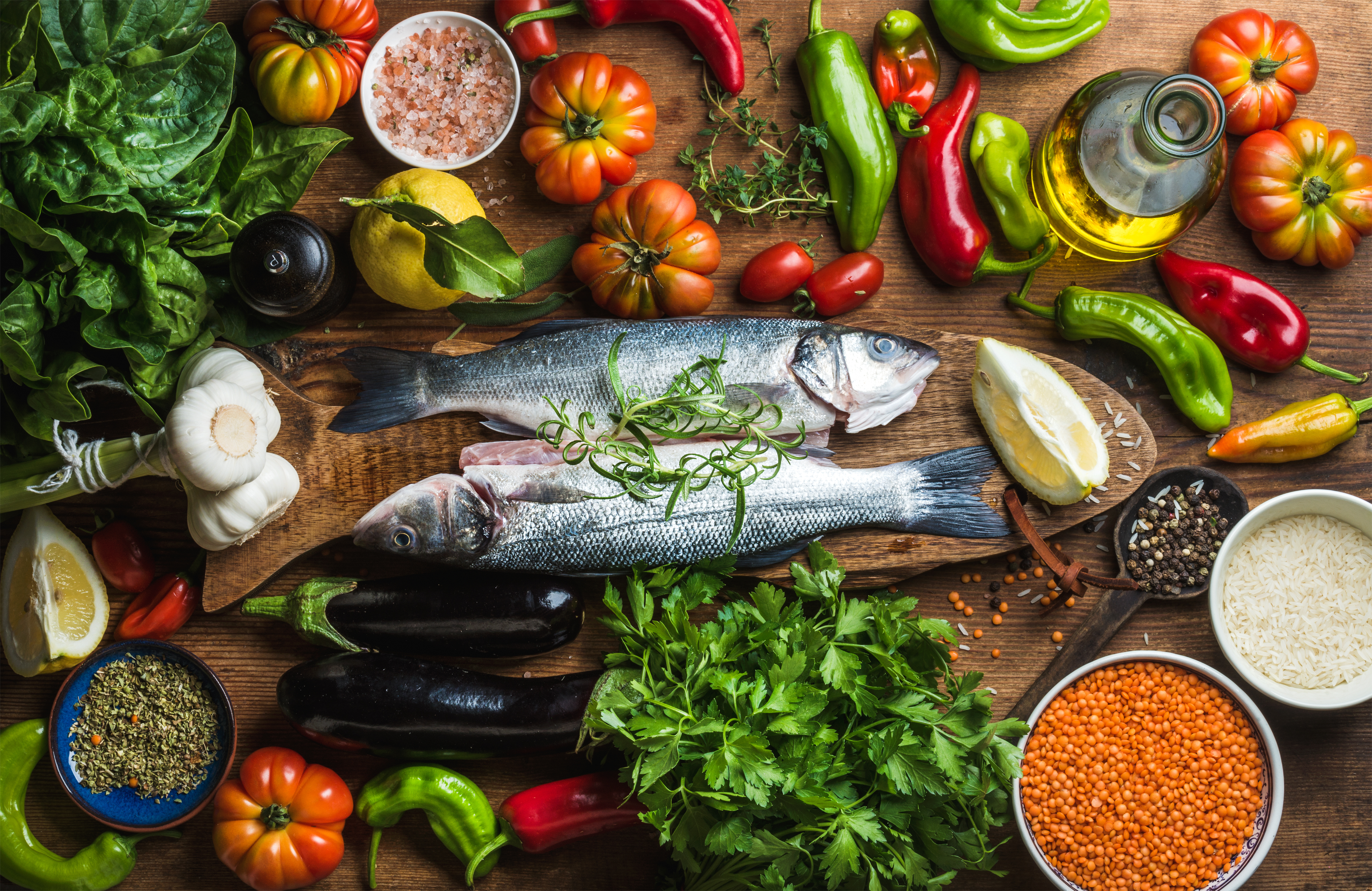 Raw uncooked seabass fish with vegetables, grains, herbs and spices on chopping board over rustic wooden background
