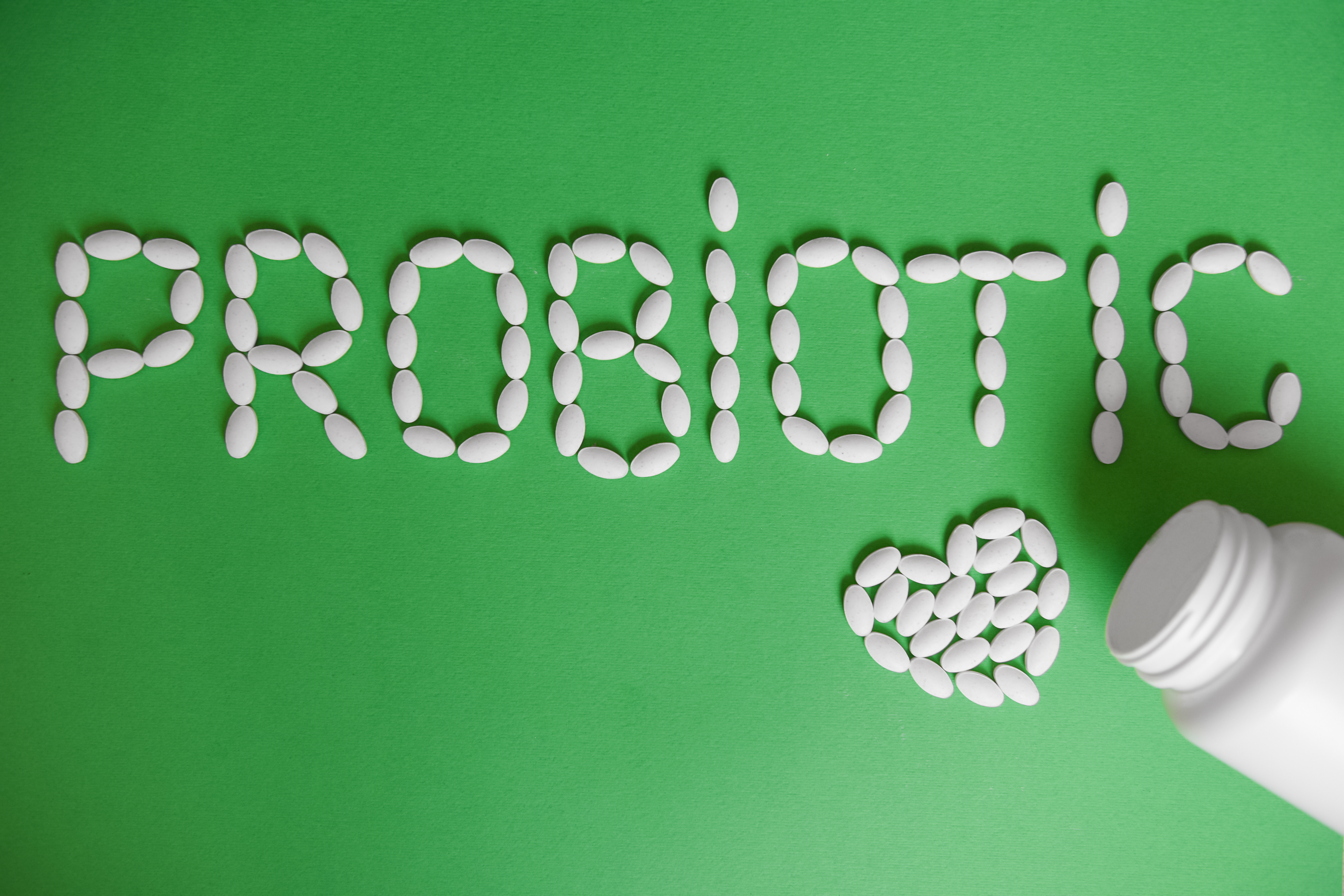 Word probiotic on a green background. probiotic capsules for health.