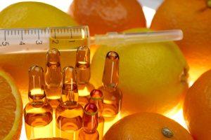 Vitamin C. glass ampoules set , syringe among the fruits of oranges and lemons