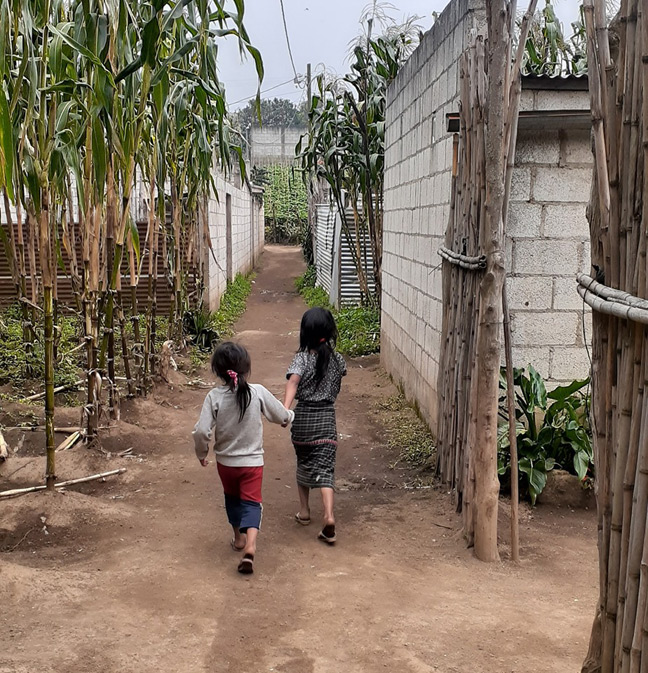 Giving children a brighter future. This is a picture of two Guatemalan girls holding hands and walking away from the camera.