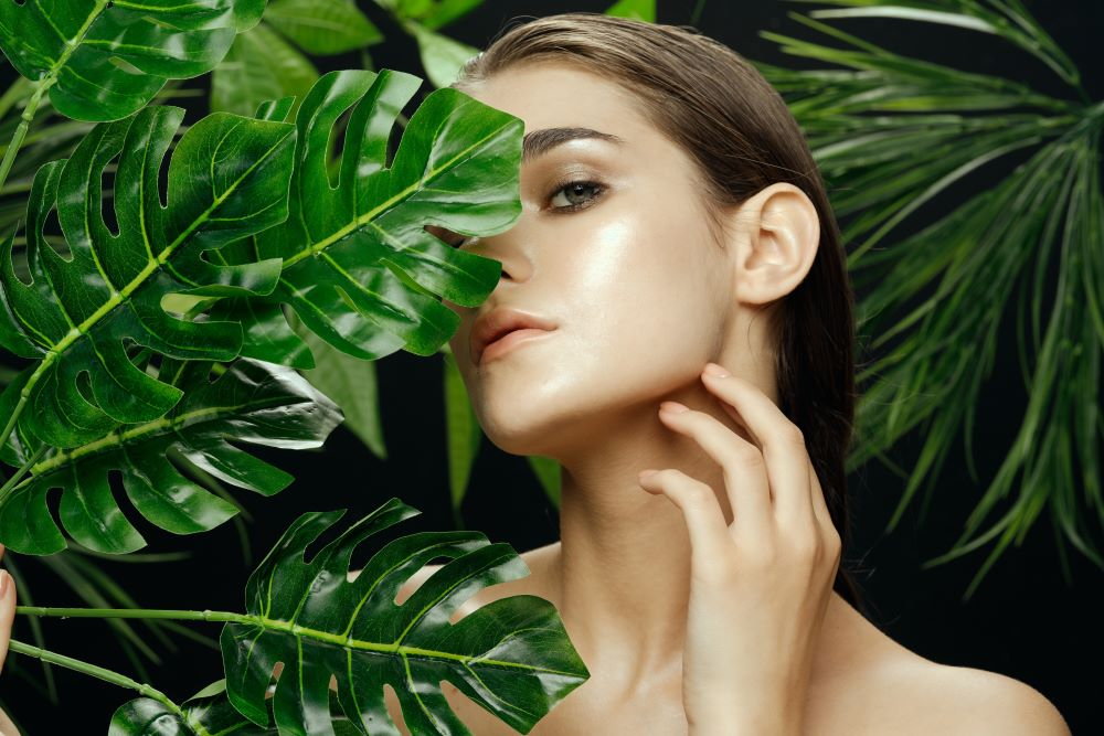 Photo of woman from neck up with hair tied back standing in tropical plants