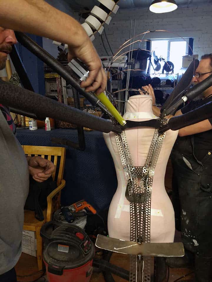 Crit Killen measures for wing attachment mount on mosquito mascot's welded steel shoulder frame and chassis