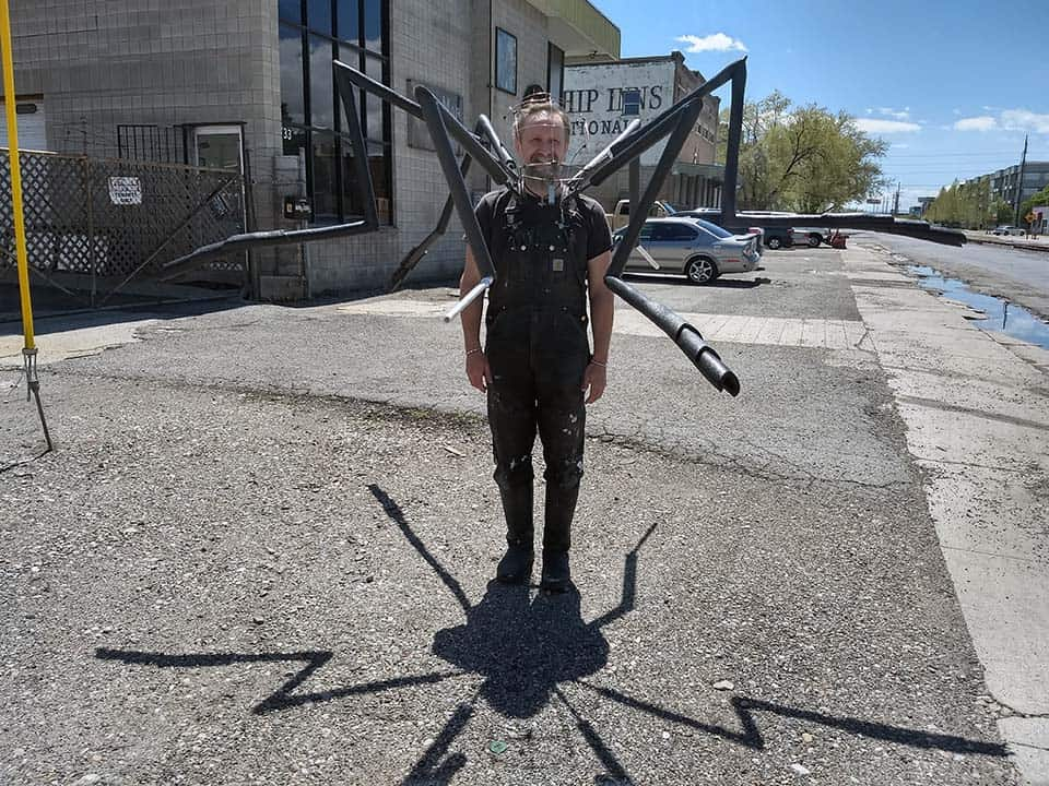 Hraefn Wulfson wearing the new shoulder chassis of custom mosquito mascot with legs attached, casting an interesting shadow