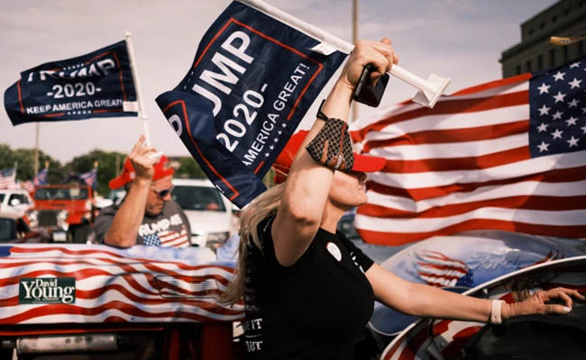 Trump supporters carried signs and waved American flags during a motorcade in Des Moines. Credit: ZUMA Press, Inc.