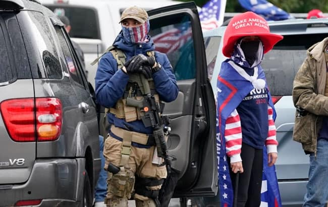 One supporter of Trump holds a gun. Credit - Associated Press