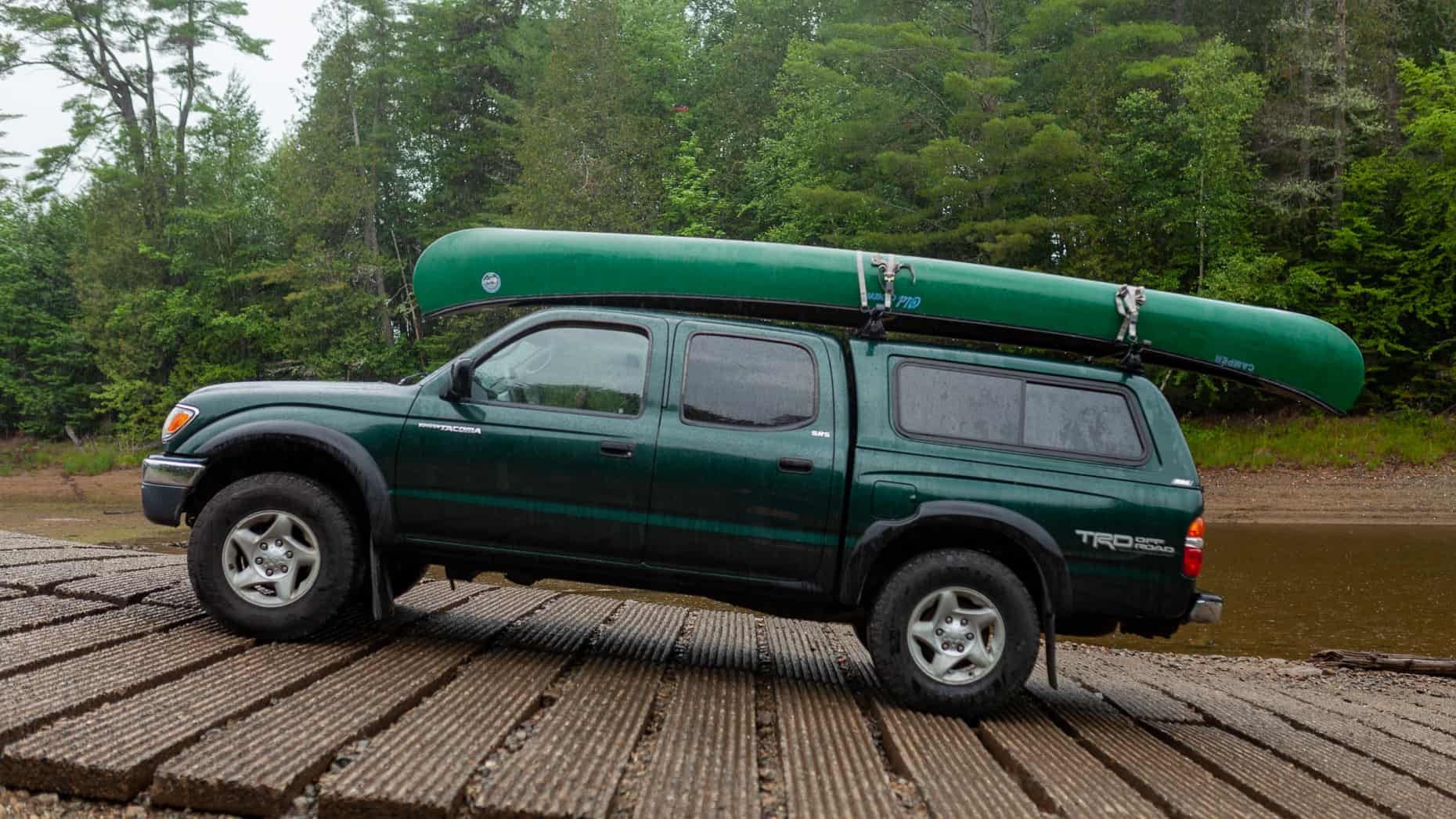 Green Toyota Tacoma on a boat launch with canoe on roof rack.