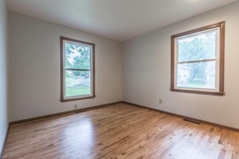 Davis bedroom with wood floor and two windows