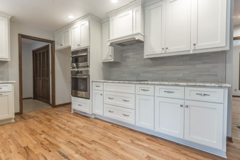 Shaker style cabinets, natural stone mist tile and wood flooring