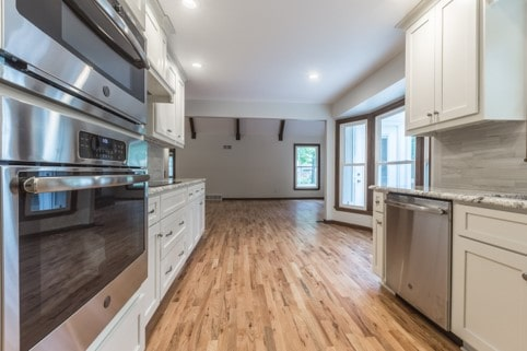 Galley kitchen with stainless appliances and dining area
