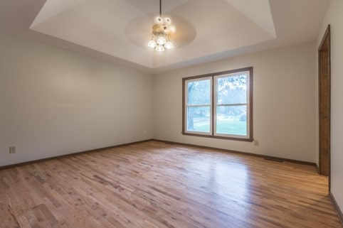Master bedroom with a recessed or tray ceiling