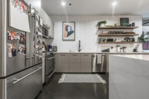 Stainless appliances with new white tile and countertop