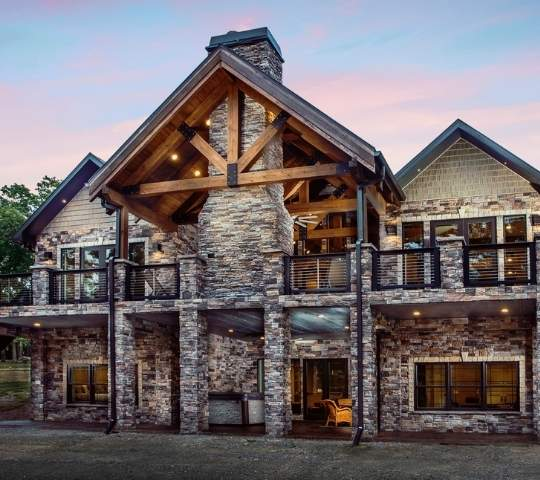 photo of timber frame home with stone facade and stone stacked supports for upper deck and fireplace. Large outdoor covered porch living space over a covered porch on lower level