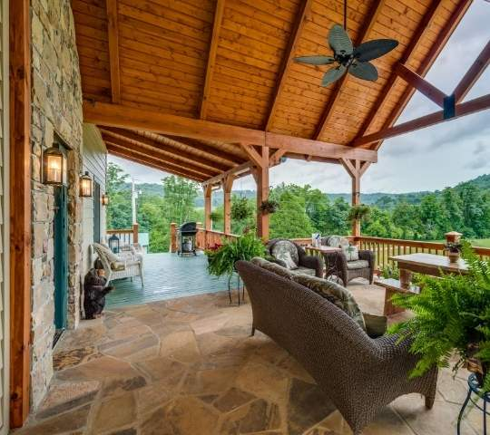 photo of covered porch outdoor living space with ceiling fan, stone floor and stone wall of home