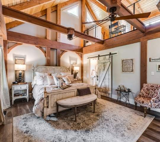 photo of master bedroom with soaring a-frame exposed wood support beams for ceiling, wood exposed ceiling and loft area