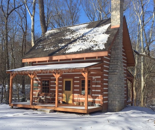 Photo of traditional chink log cabin with upper loft and covered front porch. Taken in the snow