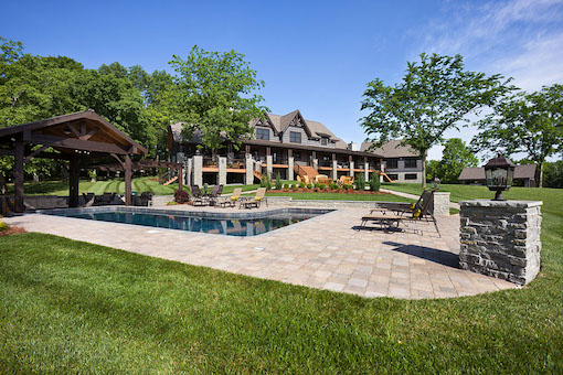 photo of timber frame estate home with outdoor living swimming pool gazebo and gardens