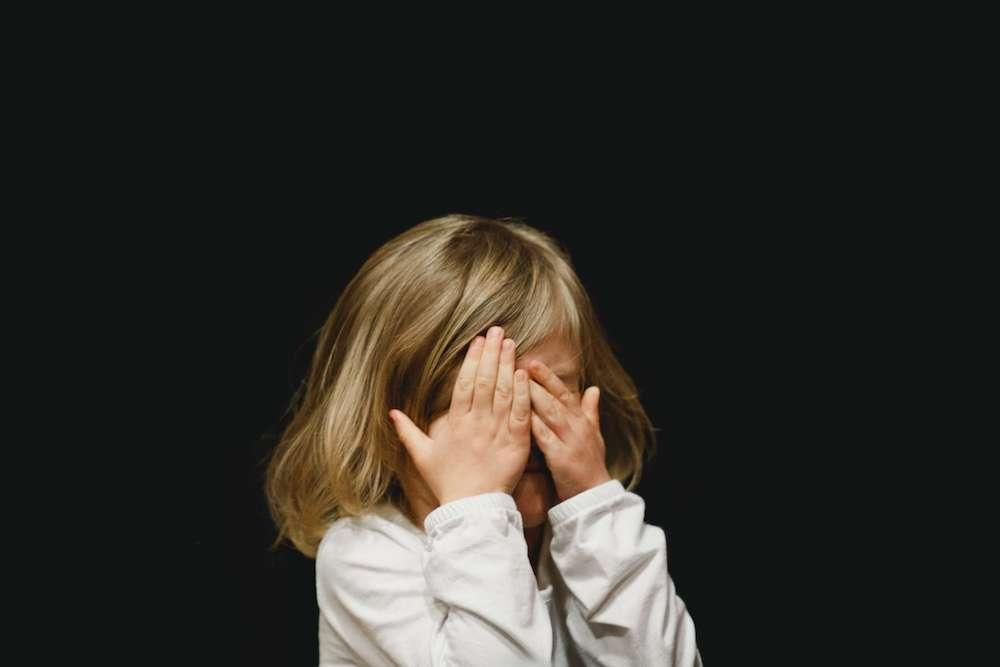 Little girl covers her eyes afraid of the dark