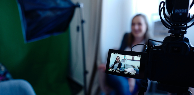 woman in front of video camera recording talking head presentation