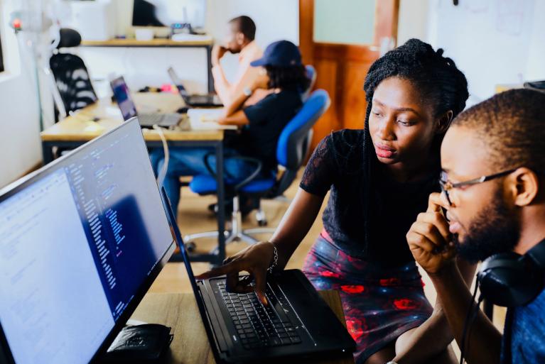 man and woman looking at computer monitor showing code