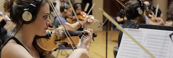 woman plays violin as part of orchestra while wearing studio headphones