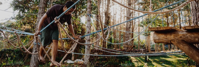 man walking across rope bridge among treetops