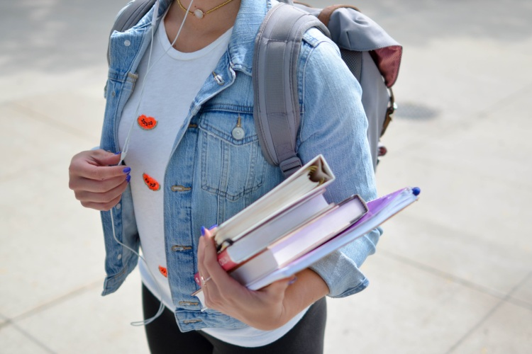 college high school student wearing backpack holding textbooks