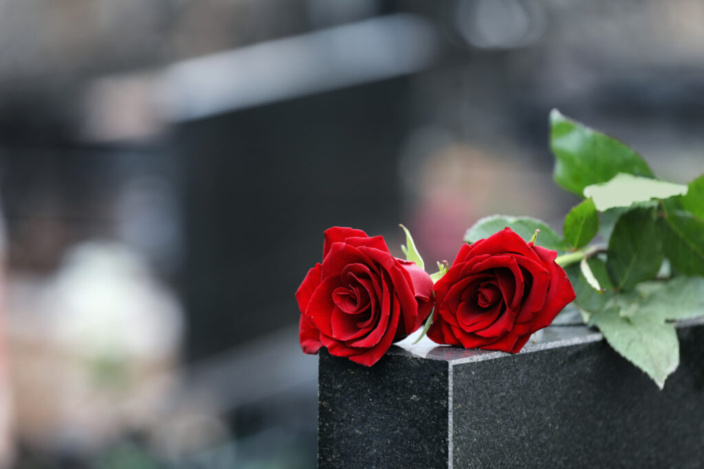 Red,Roses,On,Black,Granite,Tombstone,Outdoors,,Space,For,Text.