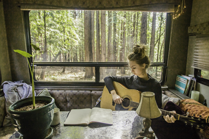 Sylvia Grape playing guitar in her home