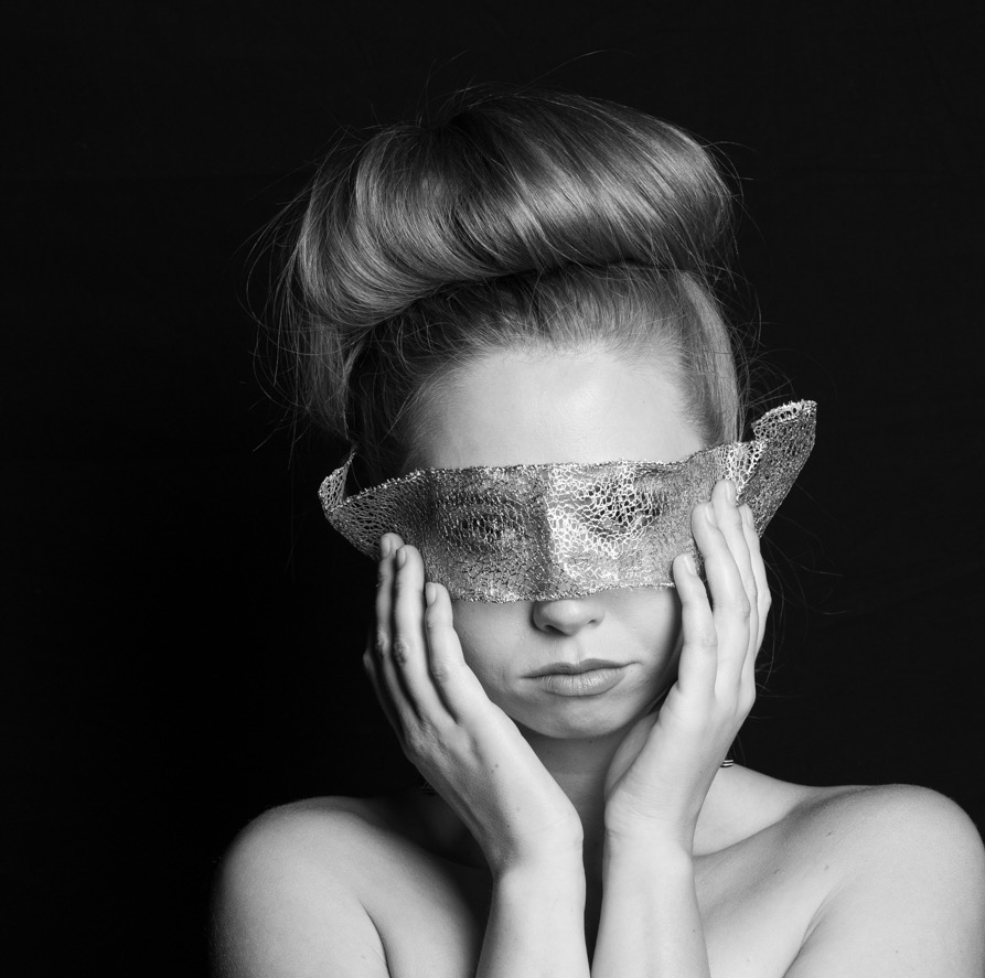 Black and white photo of Sylvia Grape holding cloth over her eyes