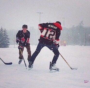 Teenage boys playing hockey on a public field.