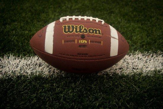 A football sitting on an empty field. - Canva