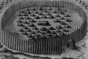 Black and white photograph of an engraving of a Native village with the chief's house in the center, surrounded by huts of other principal men, and fortified by a circular arrangement of tall palings that spiral to a narrow opening at the entrance. Engraved by Theodor de Bry.