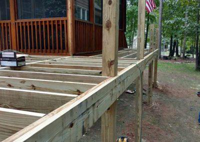 Deck being built around screened porch