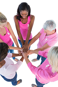 Group of women wearing pink and ribbons for breast cancer puttin