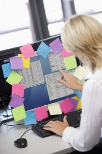 Businesswoman in office pointing at monitor with notes on it