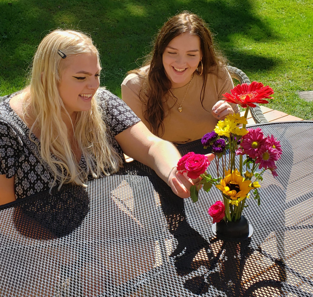 girls looking at flowers on a patio table,patio table setting,patio table umbrella hole,flower creation station