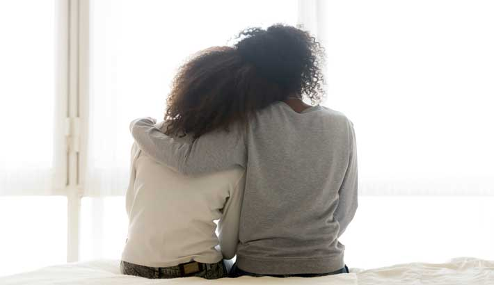 Two women sitting, one embracing her arm around the other leaning on each other