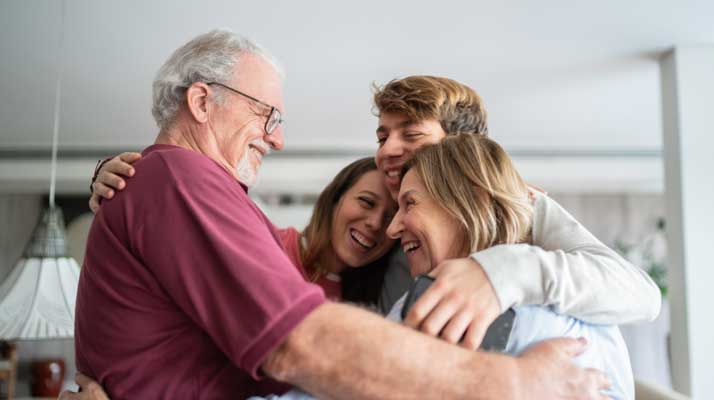 Family understanding each other and joining into a group hug with parents, daughter and son