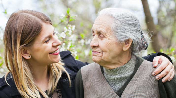 Young woman volunteer embracing an elderly woman smiling
