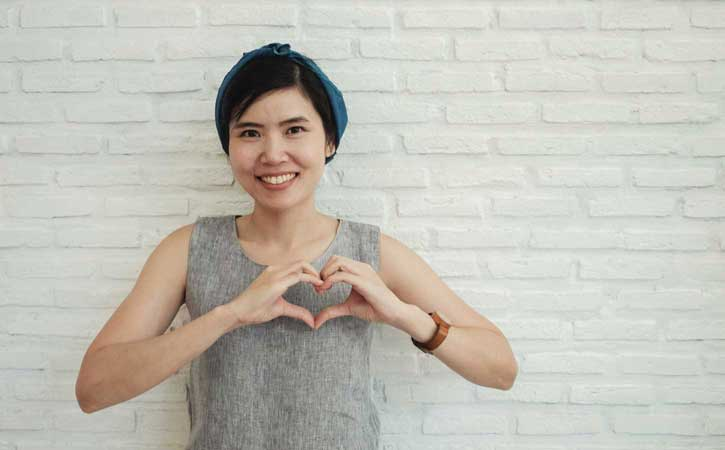 Get support, young woman supporting the idea of reaching and forming a heart with her hand