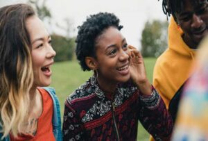 Smiling coloured woman with a group of friends outside