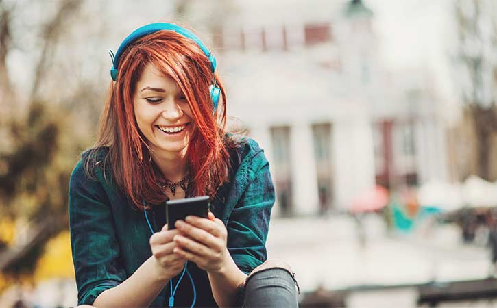 Young woman smiling listening to music and looking at her phone